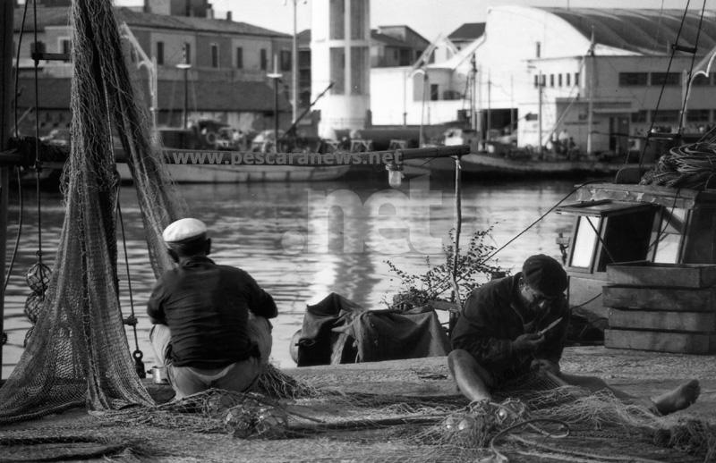 Pescatori riparano una rete sulla banchina