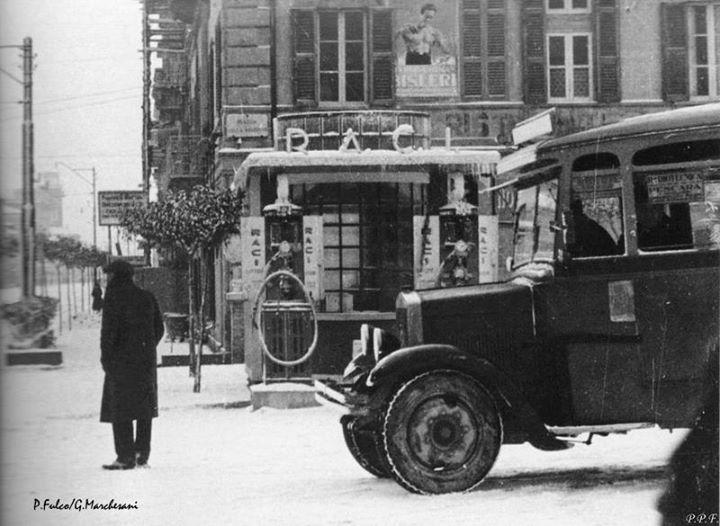 Auto d'epoca in primo piano con piazza della Repubblica innevata ed un primitivo distributore di carburante. Dietro l'albergo del Leon D'Oro. - P. Fulco